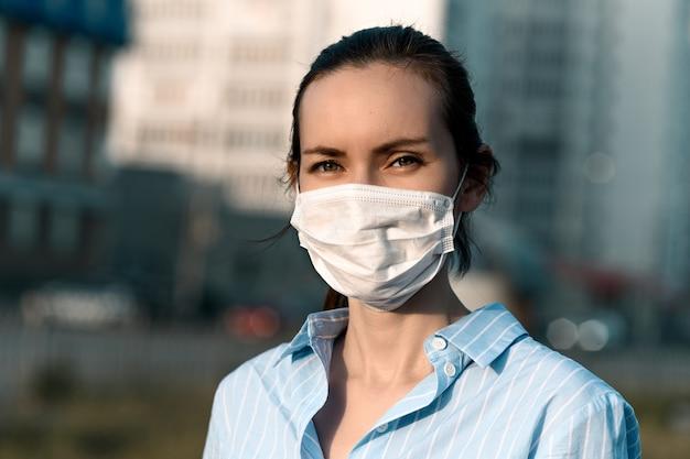 Kaukaski brunetka kobieta w masce medycznej na ulicy, koronawirus
