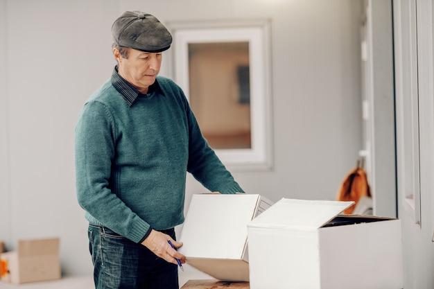 Kaukaski chłop pakuje przesyłki w pudełku stojąc na ganku.