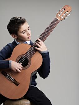 Kaukaski chłopiec gra na gitarze akustycznej.