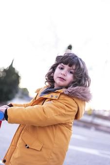 Kaukaski chłopiec jeździ na skuterze