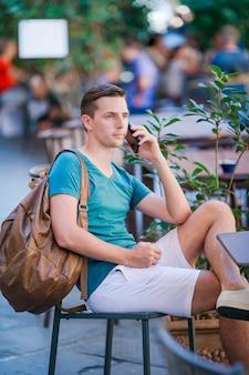 Kaukaski chłopiec trzyma telefon na zewnątrz na ulicy. człowiek za pomocą smartfona.