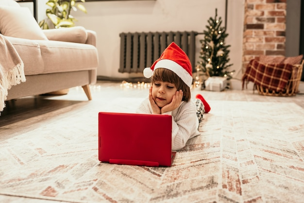 Kaukaski chłopiec w białym swetrze i czerwonej świątecznej czapce na dywanie w pokoju i oglądający laptopa