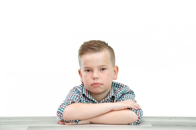 Kaukaski chłopiec w wieku szkolnym w kraciastej koszuli na jasnym odosobnionym tle siedzi z założonymi rękami