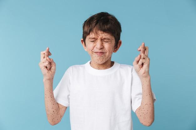 Kaukaski chłopiec z piegami na sobie białą koszulkę na co dzień, trzymając kciuki i błagając o szczęście na białym tle na niebieskiej ścianie
