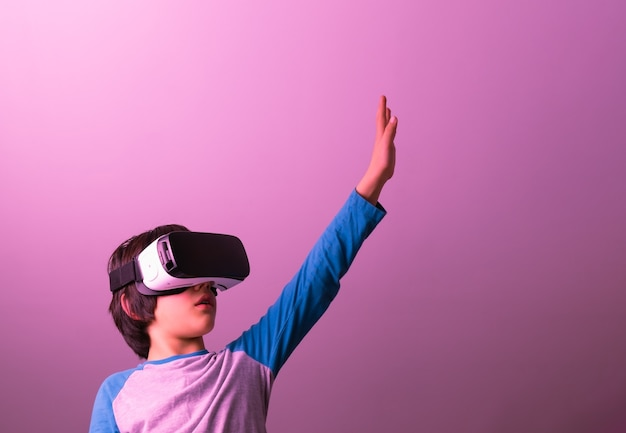 Kaukaski chłopiec z prostymi włosami w okularach wirtualnej rzeczywistości i szaro-niebieskim ubraniu z podniesioną ręką po lewej stronie