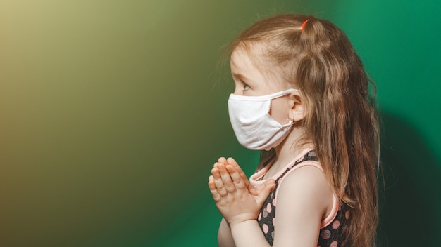 Kaukaski chora dziewczynka w masce medycznej podczas epidemii koronawirusa modli się na zielonym tle zbliżenie 2021. miejsce.