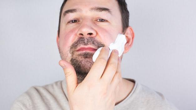 Kaukaski ciemnowłosy mężczyzna nakłada piankę do golenia na brodę, patrząc na aparat z uśmiechem