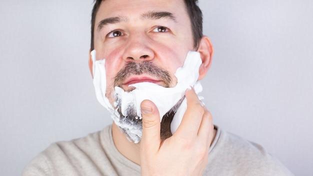 Kaukaski ciemnowłosy mężczyzna nakładający piankę do golenia na brodę, patrzący na uśmiechnięty
