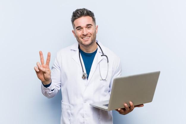 Kaukaski doktorski mężczyzna trzyma laptop pokazuje numer dwa z palcami.