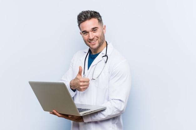 Kaukaski doktorski mężczyzna trzyma laptop uśmiecha się kciuk up i podnosi