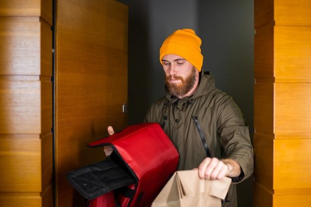 Kaukaski dostarcza pudełko do obsługi mężczyzny z jedzeniem w środku, podaje klientowi w drzwiach. usługa dostawy podczas covid19.