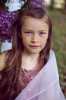 Kaukaski dziecko dziewczynka siedem lat w fioletowej sukience stoi w przyrodzie z bzami