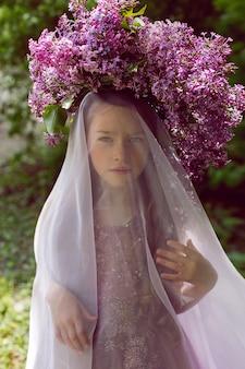 Kaukaski dziecko dziewczynka siedem lat w fioletowej sukience stoi w przyrodzie z wieńcem bzów