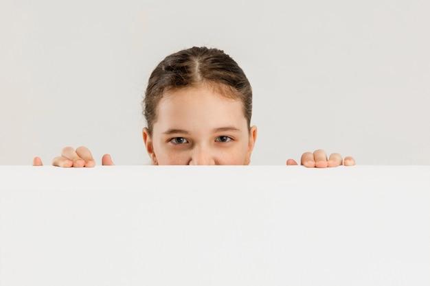 Kaukaski dziewczyna na białym tle na białej ścianie copyspace koncepcja edukacji dzieciństwa emocje