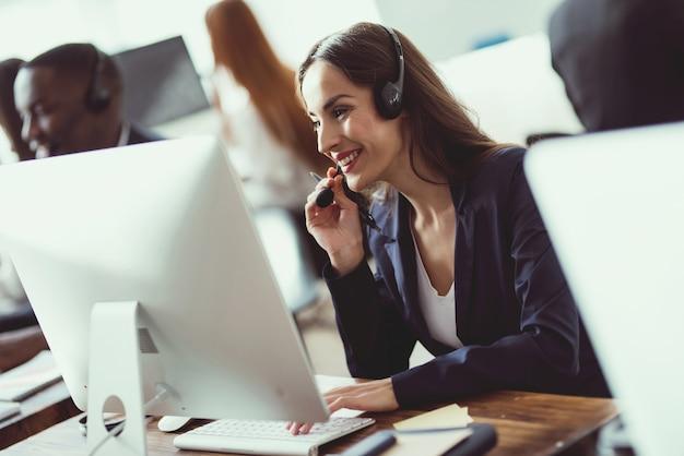 Kaukaski dziewczyna patrzy na pracę w call center.