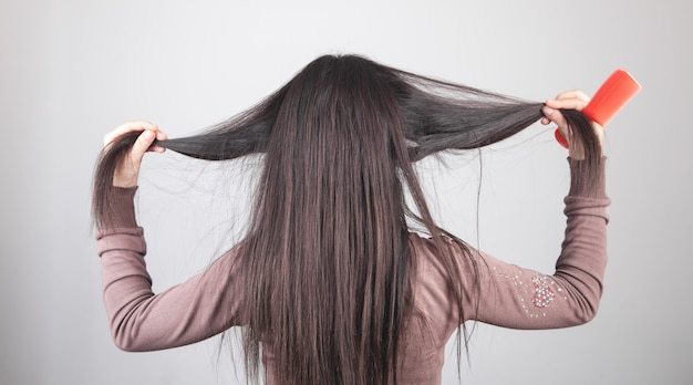 Kaukaski dziewczyna pokazując włosy grzebieniem w dłoni.