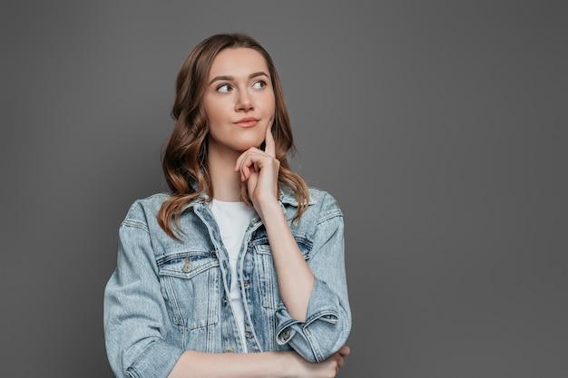 Kaukaski dziewczyna student myśli i odwracając na białym tle na ciemnoszarej ścianie. pomysł na koncepcję. skopiuj miejsce