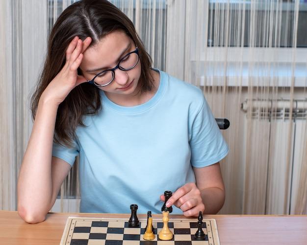 Kaukaski dziewczyna w okularach myśli gra w szachy w domu podczas kwarantanny