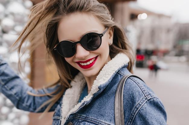 Kaukaski dziewczyna z wyrazem twarzy zadowolony spacerując po mieście w wiosenny poranek i śmiejąc się. plenerowe ujęcie wspaniałej białej kobiety w ciemnych okularach przeciwsłonecznych w dżinsowym stroju.