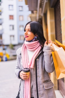 Kaukaski dziewczyna zakupy w mieście z papierowymi torbami i kawą na wynos