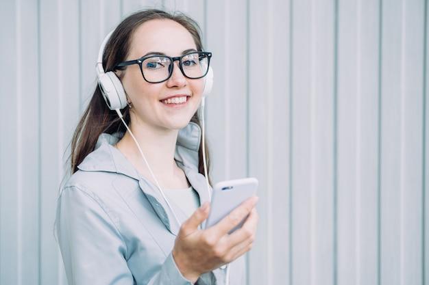 Kaukaski dziewczyna ze słuchawkami uśmiecha się i słucha muzyki