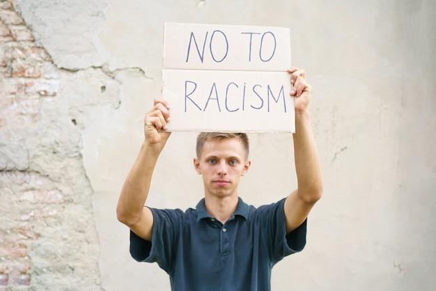 Kaukaski facet wyszedł na znak protestu przeciwko rasizmowi z plakatem w dłoniach przedstawiający młodego mężczyznę...