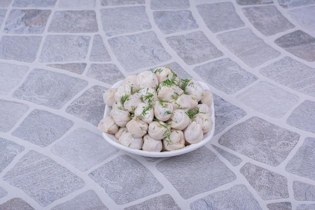 Kaukaski farsz z ciasta chinkalowego w białym talerzu.