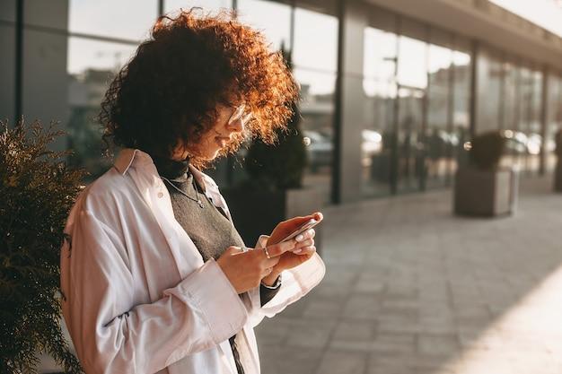 Kaukaski freelancer z kręconymi włosami koncentruje się na swoim telefonie, nosząc okulary i pozując na zewnątrz