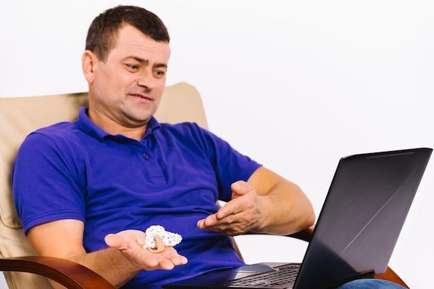 Kaukaski głuchy mężczyzna z uszkodzeniem słuchu trzyma w dłoni aparat słuchowy i pokazuje go