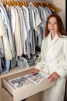 Kaukaski gospodyni młoda kobieta w białym szlafroku frotte trzyma pojemnik z bielizną, skarpetkami i majtkami. przechowywanie ubrań.