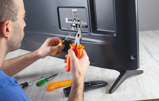 Kaukaski inżynier naprawy telewizora w domu.