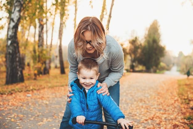 Kaukaski kobieta i jej syn, jazda na rowerze w parku, ucząc go