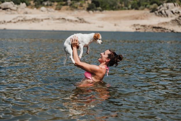 Kaukaski kobieta i pies ładny jack russell pływanie w jeziorze i wspólną zabawę. koncepcja wakacji i relaksu