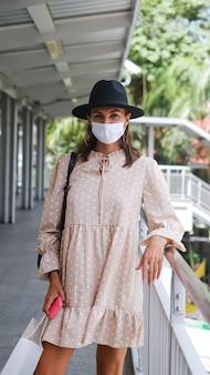 Kaukaski kobieta idzie na przejściu metra w masce medycznej podczas pandemii w bangkoku.