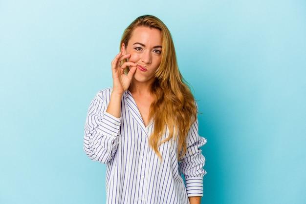 Kaukaski kobieta na białym tle na niebieskim tle z palcami na ustach dochowania tajemnicy.