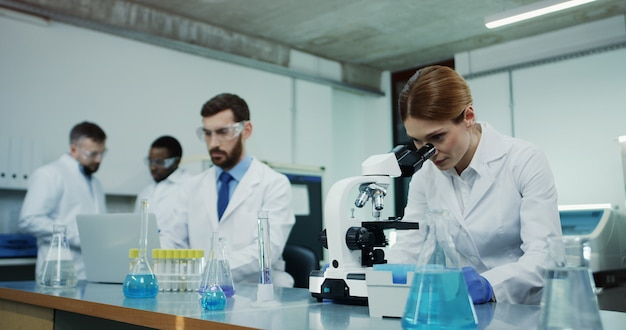 Kaukaski kobieta naukowiec w białym szlafroku, patrząc w mikroskop podczas przeprowadzania dochodzenia, a jej kolega testuje ciecz w tubie przy komputerze.