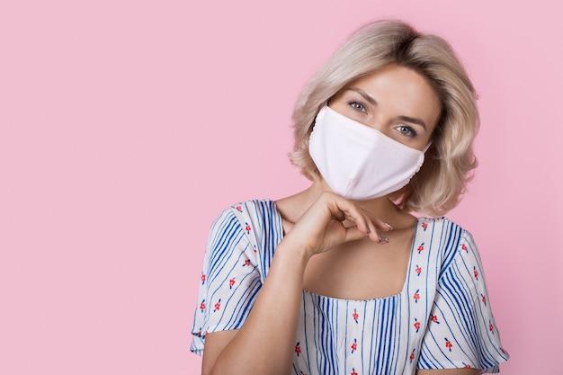 Kaukaski kobieta o blond włosach ubrana w letnią sukienkę uśmiecha się do kamery z maską medyczną