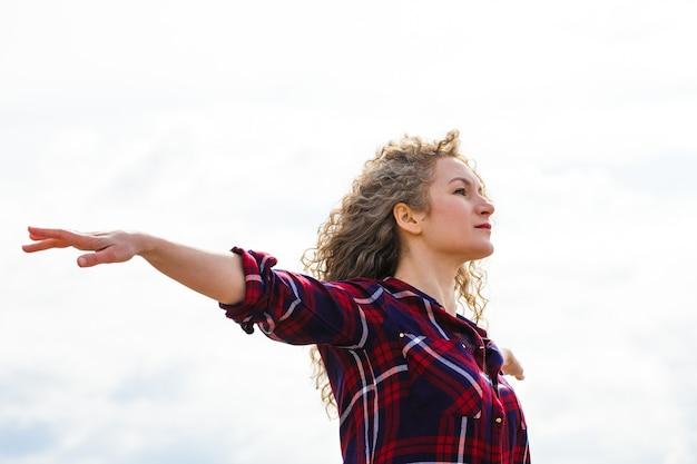 Kaukaski kobieta relaks na plaży z otwartymi ramionami, ciesząc się wolnością kręcone włosy na wietrze