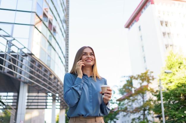 Kaukaski kobieta rozmawia przez telefon trzymając kawę, aby przejść. europejka sukcesu, rozmawiająca przez telefon, stojąca na nowoczesnym biurowcu