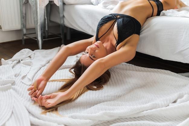Kaukaski kobieta sobie bieliznę w ustawienie sypialni buduar w różnych pozach.