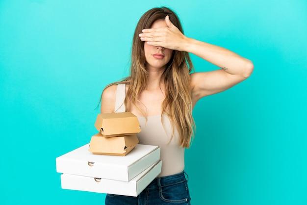 Kaukaski kobieta trzyma pizze i burger na białym tle na niebieskim tle zasłaniając oczy rękami. nie chcę czegoś widzieć