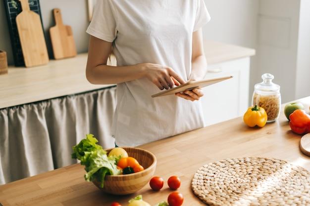 Kaukaski kobieta używa komputera typu tablet w kuchni przygotowując przepis przeczytać sałatkę