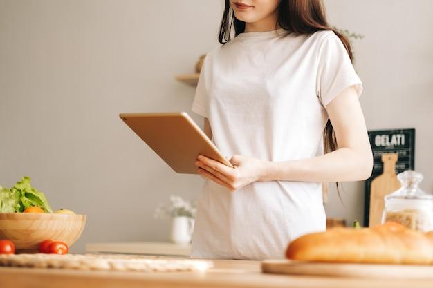 Kaukaski kobieta używa komputera typu tablet w nowoczesnej kuchni