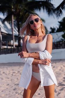 Kaukaski kobieta w bikini i okulary przeciwsłoneczne na tropikalnej plaży