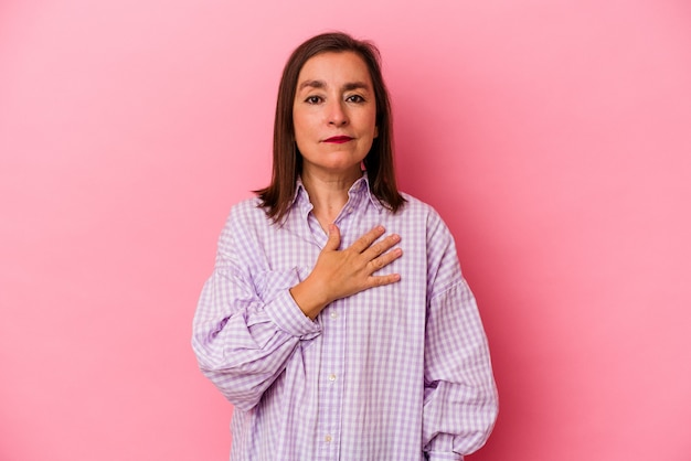 Kaukaski kobieta w średnim wieku na białym tle na różowym tle składa przysięgę, kładąc rękę na klatce piersiowej.