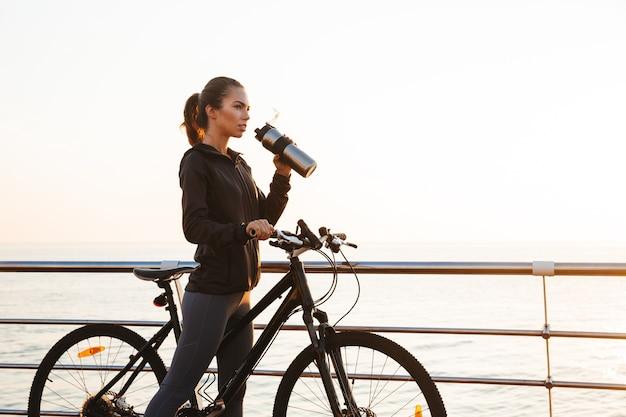Kaukaski kobieta wody pitnej podczas jazdy na rowerze na promenadzie, podczas wschodu słońca nad morzem