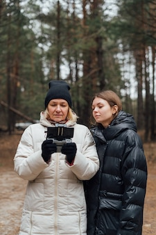 Kaukaski kobieta z córką dorosłych latający dronem w lesie jesienią.