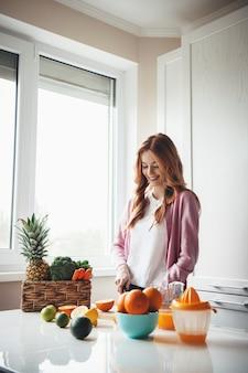 Kaukaski kobieta z rudymi włosami i piegami, uśmiechając się podczas krojenia owoców na świeży sok