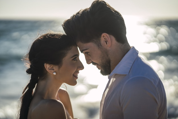 Kaukaski kochająca para ubrana w białe ubrania i przytulanie na plaży podczas sesji ślubnej