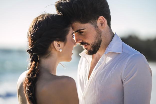 Kaukaski kochająca para ubrana w białe ubrania i przytulanie na plaży podczas sesji zdjęciowej ślubu